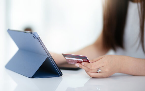 Focus on hand young asian woman holding mock up of creditcard and using digital tablet to shopping or paying online