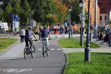 Fototapeta Młodzi mężczyzni, chłopaki jadą na rowerach po ścieżce rowerowej we Wrocławiu.  obraz