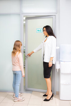 Beautiful woman opens the door in a medical clinic for a little girl and invites to the doctor's office