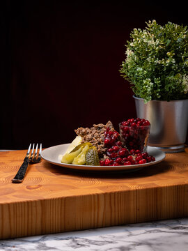 Traditional Finnish cuisines; closeup of sautéed reindeer on a plate with lingonberry jam and pickles on the side.
