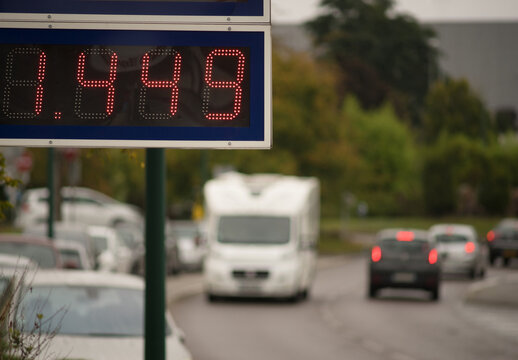 LED display board with gasoline price and blurred cars in the background