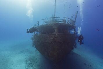 SCUBA divers exploring a caribbean ship wreck