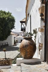 Klimatyczna uliczka w małym miasteczku Betancuria na Fuerteventurze, gliniany wazon na tle białych budynków.