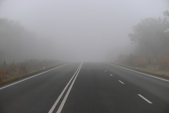 Bad weather driving - foggy hazy country road. Motorway - road traffic. Winter-autumn time.