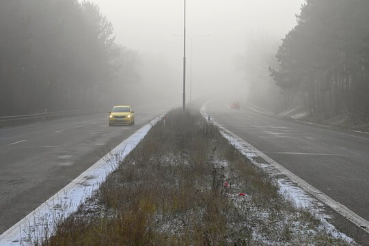 Car on the road in the fog. Autumn landscape - dangerous road traffic in winter season.