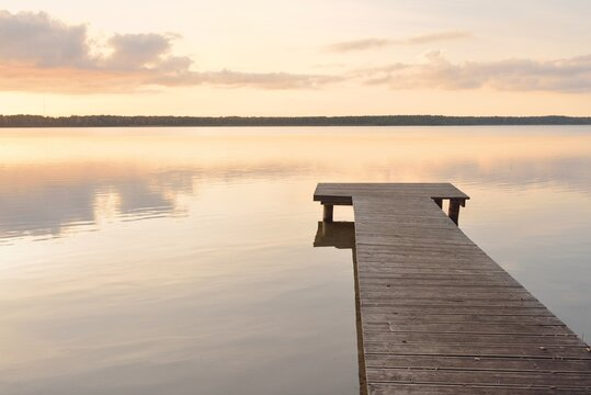 Forest lake (river) at sunset. Wooden pier. Glowing clouds, symmetry reflections in a still crystal clear water. Idyllic landscape. Nature, ecology, ecological reserve, ecotourism, hiking, vacations
