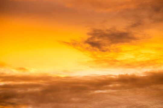 Der Himmel leuchtet beim Sonnenuntergang in intensivem Orange. Einige Wolken sind zu sehen.