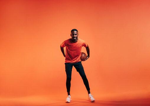 Young smiling sportsman dribbling basket ball in studio over orange background
