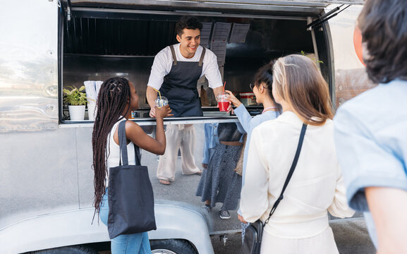 Queue of people to the food truck. Smiling salesman gives drinks to customers.