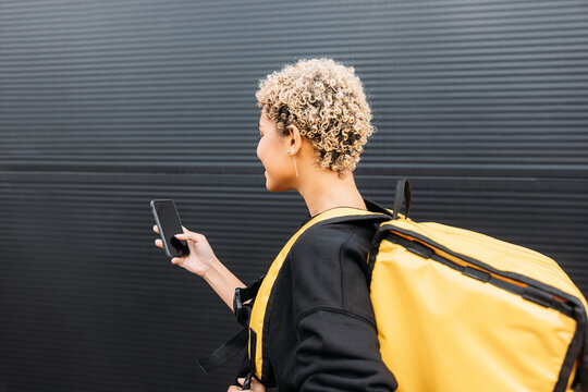 Side view of confident delivery woman with bag standing on a sidewalk holding a smartphone