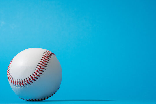 Close-up image of baseball ball on blue background in perspective. Minimalist photo of baseball ball with harsh shadow. Stylish shot of a ball from baseball game with copy space.