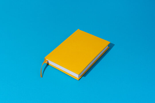 Photo of closed yellow notebook over blue background with copy space. Minimalist image of closed diary as back to school concept.