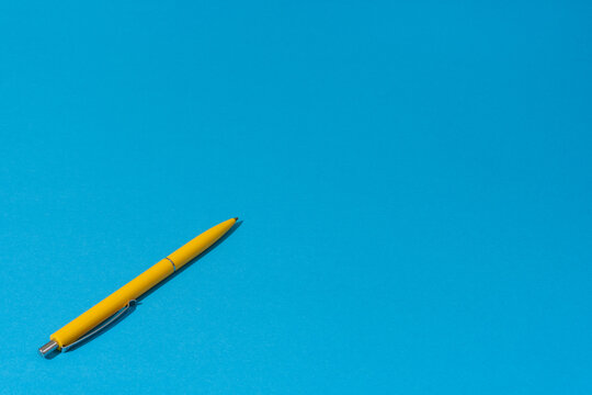 Perspective view of ballpoint pen on the blue background. Minimalist photo of yellow pen over blue background with copy space.