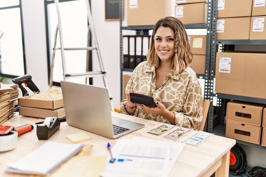 Young hispanic woman smiling confident working using calculator at office