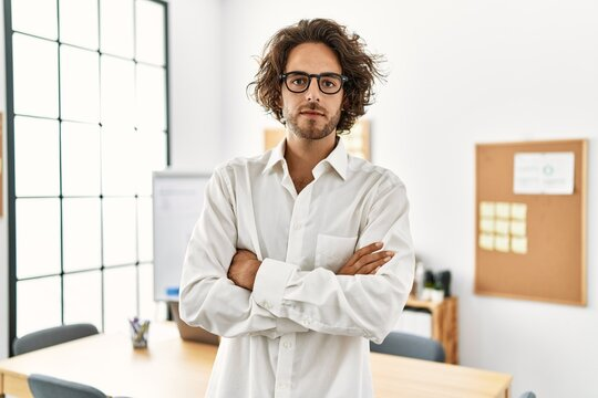 Young hispanic businessman with serious expression standing with arms crossed gesture at office.