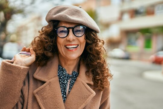 Middle age hispanic woman smiling happy shopping at the city.