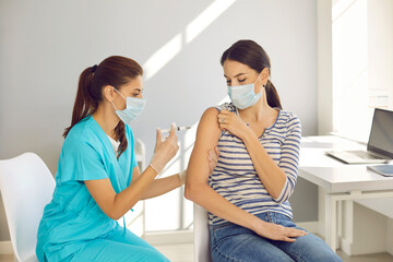 Fototapeta Highly qualified nurse gives Covid-19 vaccine to responsible female patient at modern medical center. Beautiful young woman wearing mouth covering getting flu shot during seasonal vaccination campaign obraz
