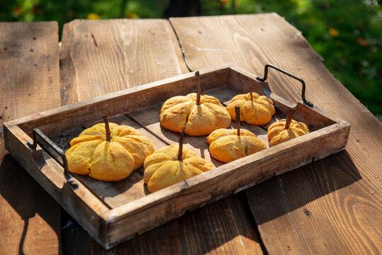 Pumpkin cookies on desk on green grass