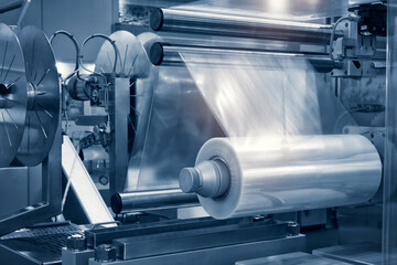 Obraz The operation of automatic plastic bag production machine with lighting effect. Close-up of the roller of the plastic bag production machine in the light blue scene. - fototapety do salonu