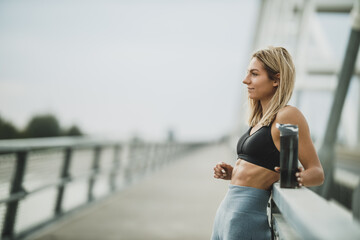 Obraz Woman Holding Water Bottle And Preparing For Outdoor Working Out - fototapety do salonu