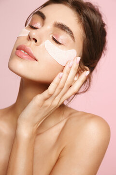 Skin care and cosmetology. Beautiful natural woman with healthy skin, applying under eye patches from puffiness and dark circles, pink background