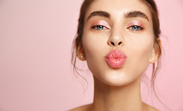 Cosmetics and skin care. Portrait of beautiful woman pucker lips, kissing, showing natural clean facial skin, standing over pink background