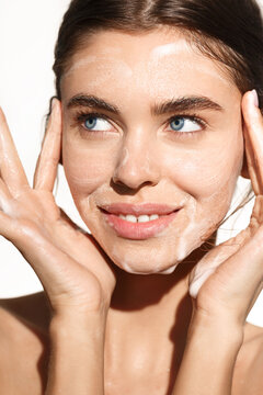 Vertical portrait of young woman washing her face with cleansing foam gel, smiling happy, cleaning her facial skin, standing over white background