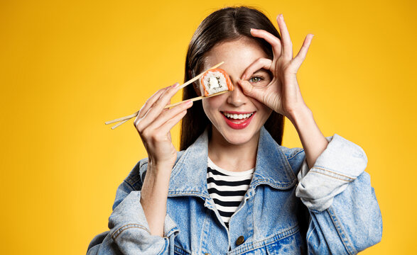 Smiling woman holding sushi, sashimi with chopsticks, showing okay sign and looking happy, eating delicious takeaway foor, concepf of food delivery, yellow background