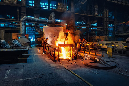 Metal cast process in blast furnace in metallurgical plant or factory. Liquid iron molten metal pouring in container, heavy industry background.