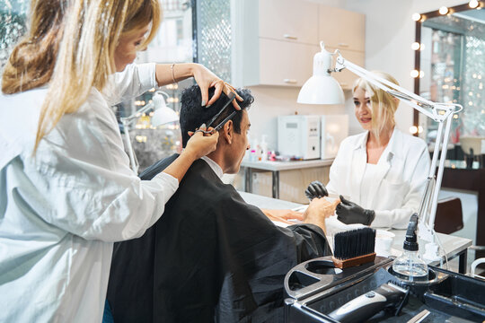 Woman manicurist grinding down client nails during haircut