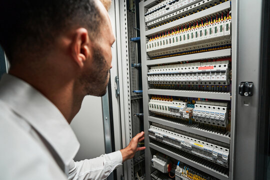 Data center worker reaching for electrical switch inside cabinet