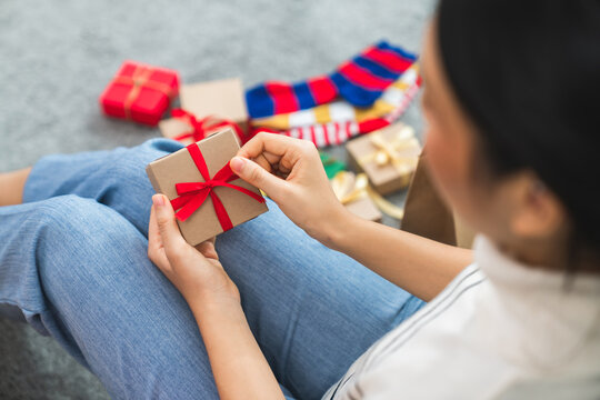 Young woman hands holding open gift box with red bow in the house, Concept of christmas, new year and birthday.