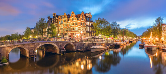 Fototapeta Amsterdam, Netherlands. Panorama of the historic city center of Amsterdam. Traditional houses and bridges of Amsterdam small town. A romantic evening and a bright reflection of houses in the water.  obraz