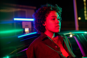 Fototapeta Young serene woman leaning against car in urban environment at night obraz