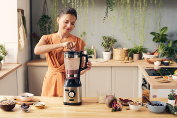 Obraz Young woman mixing ingredients of smoothie in electric blender while preparing healthy drink - fototapety do salonu