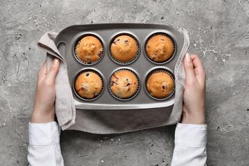 Fototapeta Woman holding baking tin with tasty cranberry muffins on grunge background obraz