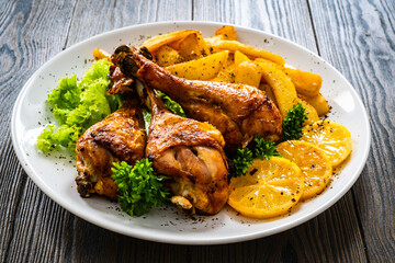 Obraz Barbecue chicken drumsticks with chips on wooden table  - fototapety do salonu