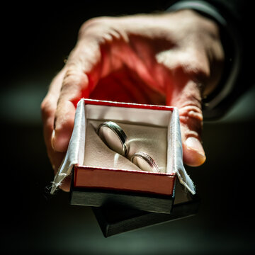 A hand holding two wedding rings in a beautiful box