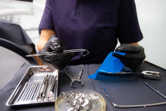 A dentist prepares a latex scarf with metal clips to treat canals and pulpitis. Pliers punch a hole in a black latex insulating napkin