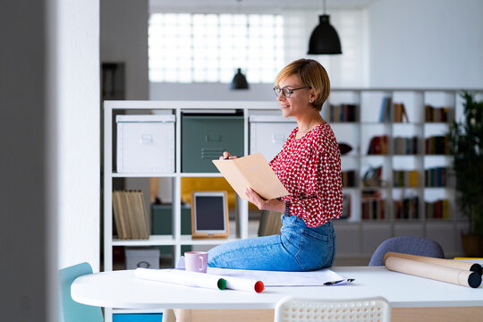 Mid adult female professional writing in diary while sitting on desk