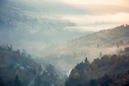 countryside mountain landscape on a foggy morning. beautiful nature scenery with trees in colorful foliage on the hills and village in the distant valley