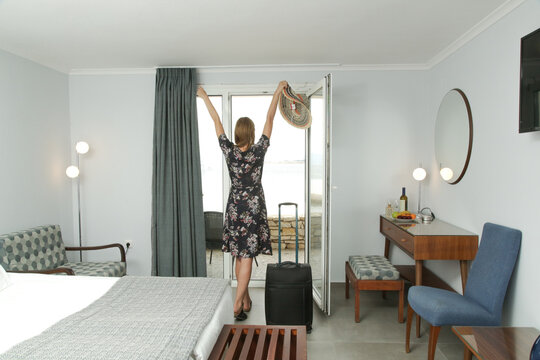Young woman with luggage in hotel room with arms raised. The first day of summer vacation.