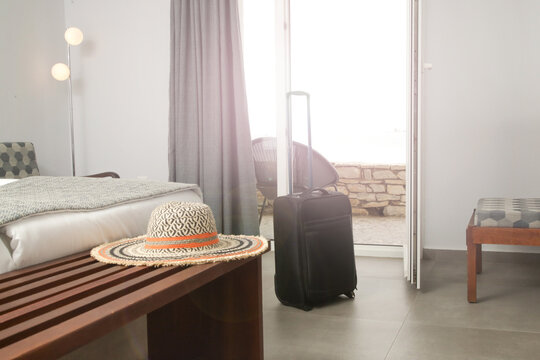 Luggage and straw hat in hotel room