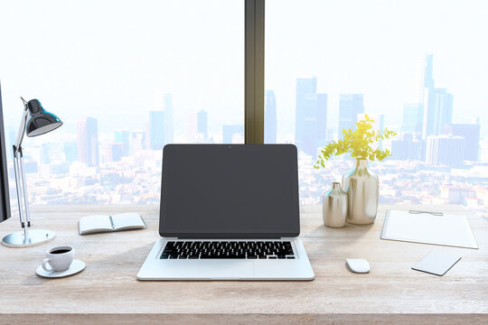 Creative designer desktop with empty laptop computer in modern interior with window and bright city view. Mock up, 3D Rendering.
