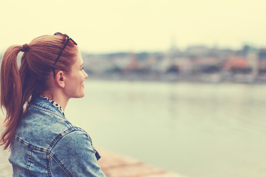 Young redhead woman looking into distance at riverbank