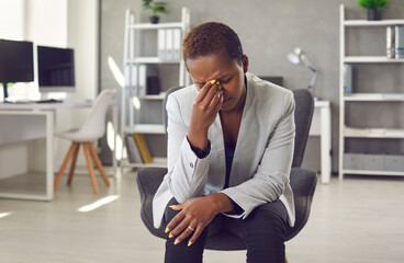 Obraz Exhausted and frustrated woman is working on difficult business task and has bad conversation. Tired african american young female company manager sitting in office in front of webcam and rubbing eyes - fototapety do salonu