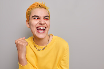 Fototapeta Pretty optimistic punk girl feels like winner celebrates success clenches fist looks happily away wears casual yellow jumper isolated on grey background blank copy space belongs to youth subculture obraz