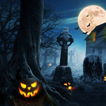 Halloween pumpkins near a tree in a cemetery with a scary house. Halloween background at night forest with moon and bats.