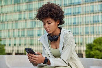 Obraz People and sporty lifestyle concept. Afro American young woman holds modern smartphone checks notification checks activity during break after workout browses internet poses against modern building - fototapety do salonu