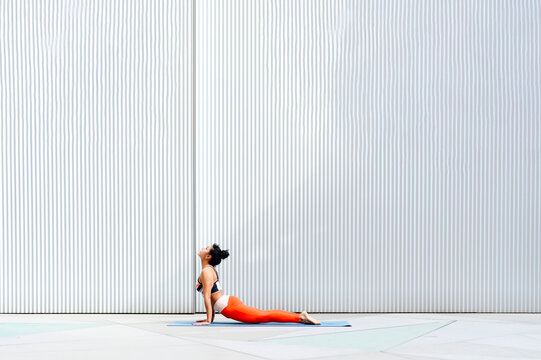 Mid adult female athlete doing cobra pose on mat by wall